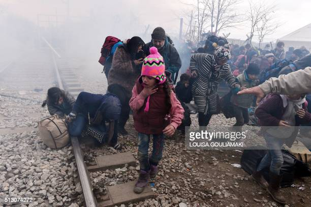 TOPSHOT A child coughs as migrants and refugees run away after Macedonian police fired tear gas at hundreds of Iraqi and Syrian migrants who tried to...