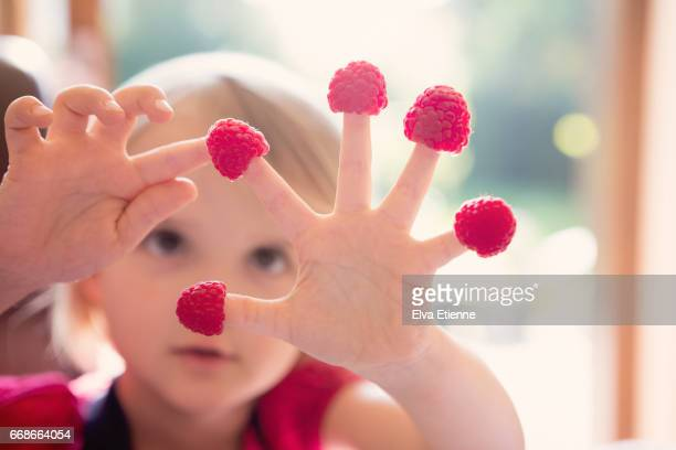 Child counting raspberries on fingers
