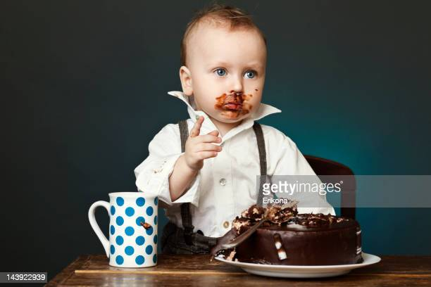 A child covered in chocolate cake on his face
