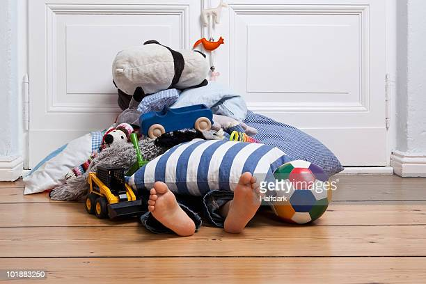 A child covered in toys, only feet visible