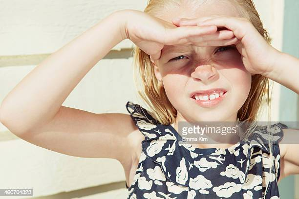 Child covering her eyes from sun glare