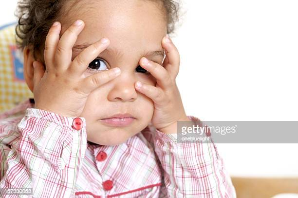 Child covering her head with hands against white background