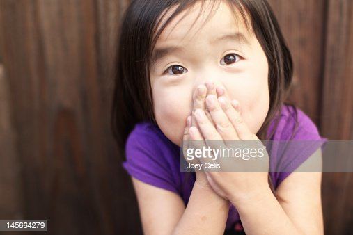 Child covering her nose and mouth