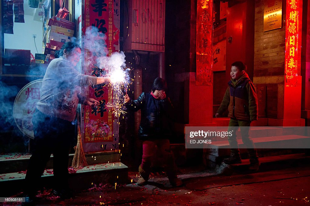 A child covers his ears as another watches a sparkler in an alleyway in Beijing during the lantern festival, which marks the end of celebrations for the Chinese new year period, on February 24, 2013. China celebrated the traditional lantern festival with food and fireworks as millions of migrant workers flowed back to the cities and smog blanketed a large part of the country. AFP PHOTO / Ed Jones