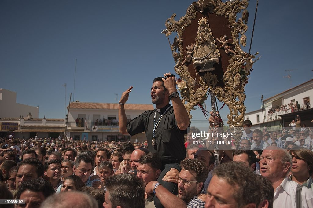A child cries after being placed onto the float an effigy of the virgin Mary as it is carried during a procession in the village of El Rocio, southern Spain on June 9, 2014 also home to the statue of the 'Madonna of the Dew' that has been worshipped since 1280. El Rocio pilgrimage is the largest in Spain with hundreds of thousands of devotees wearing traditional outfits converging in a burst of colour as they make their way on horseback and decorated carriages across the Andalusian countryside.