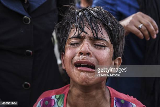 A child cries after receiving tear gas thrown by Hungarian antiriot police to disperse migrants who try to cross the Hungarian border with Serbia...