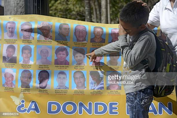 A child cries as he point at a portrait on a banner depicting disappeared people during a demo of the 'Madres de la Candelaria' a social movement...