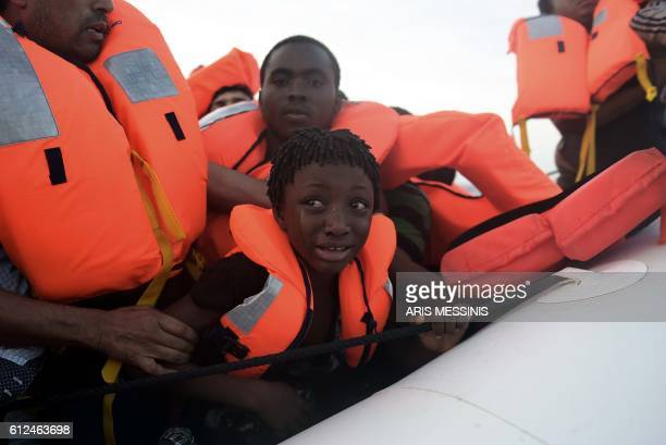 TOPSHOT A child cries as migrants are being rescued by members of Proactiva Open Arms NGO in the Mediterranean Sea some 12 nautical miles north of...