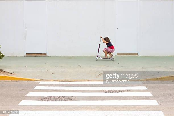 Child crouched on his scooter