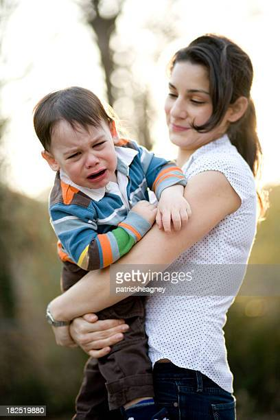 A child crying on his mothers arms