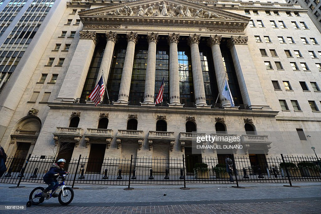 A child cycles by the New York Stock Exchange in New York March 5 2013 The Dow Jones industrial average surged to a record high at the opening bell...