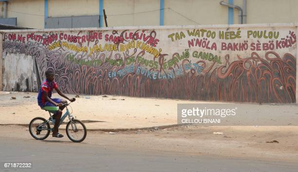 A child cycles past a graffiti reading 'Nothing can be built without book' in Conakry on April 23 2017 Conakry is hosting the 'World book capital'...