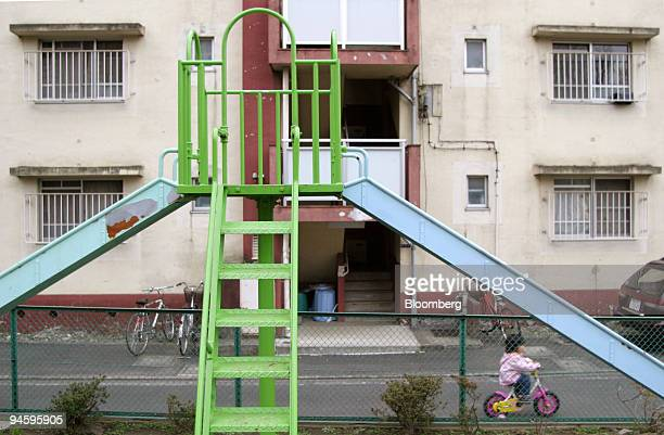 A child cycles past a metal slide at a public playground park in central Tokyo Japan March 15 2007 Thieves are taking playground slides and cemetery...