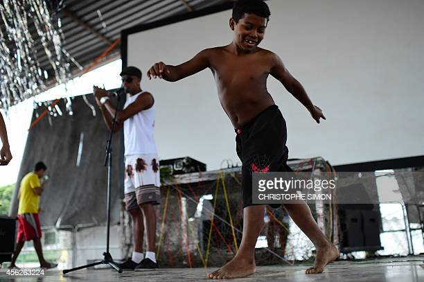 A child dances on the stage before the film projection at BrazilianFrench 'Planeta Ginga' film and music free festival at the Cidade de Deus...