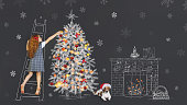 Little curly redhead girl and her puppy, decorate a fir tree drawing on chalkboard in the home. Merry Christmas, New Year and Holiday concept.