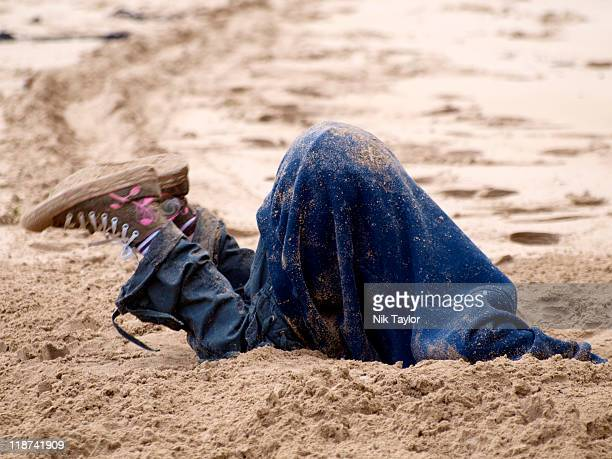 Child digging hole in sand at beach