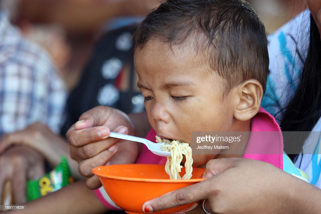 A child displaced by continuing armed conflict between the supporters of Philippine Muslim clan Sulu Sultan Jamalul Kiram III and Royal Malaysian Police in Sabah, Malaysia, eats at the arrival section on March 30, 2013 in Bonggao, Tawi-Tawi, Philippines. Following the insurgency in Sabah and the Malaysian government's subsequent crackdown on undocumented Filipinos, over 4000 people, mostly Filipino Muslims, have begun evacuating to the southern provinces of Basilan, Sulu, and Tawi-Tawi in the Philippines, with numbers expected to reach more than 100,000.