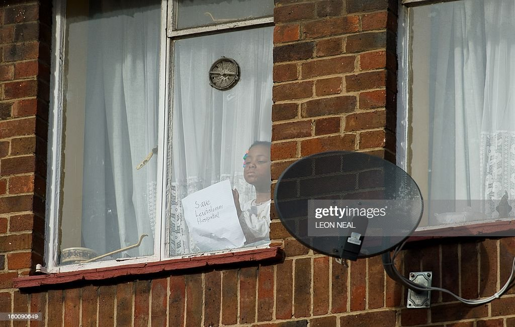 A child displays a sign reading 'Save Lewisham Hospital' from the window of a house as people take to the streets of south-east London on January 26, 2013 to protest against the proposed closure of the Accident and Emergency (A&E) and maternity units at Lewisham hospital. A Government-appointed administrator has recommended that the units be shut down to help tackle the financial crisis at the nearby South London Healthcare NHS Trust. Those protesting argue that leaving a single A&E unit for up to 750,000 people is 'ludicrous and highly dangerous'. AFP PHOTO/Leon Neal