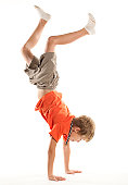 vertical photograph of a young boy doing a hand stand