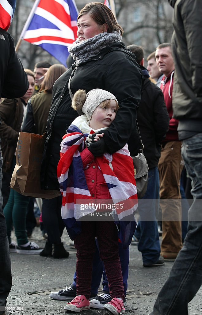 A child drapped in the British Union flag stands with loyalist protesters during a demonstration outside Belfast City Hall in Belfast on January 12, 2013 as part of an ongoing campaign opposing Belfast City Council's decision to restrict the days on which the British Union Flag will fly over the City Hall. Northern Irish demonstrators loyal to Britain clashed with nationalists and police on Saturday in fresh protests against curbs on flying the British flag, leaving four officers injured, police said. Pro-British demonstrators have taken to the streets, in sometimes violent protest, almost every night since December 3, when the city council announced it would no longer fly the Union Flag all year round at City Hall.