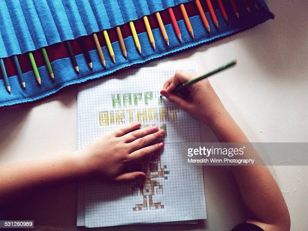 Child drawing a birthday card with colored pencil