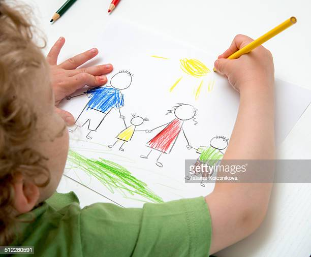 Child drawing a picture of a family