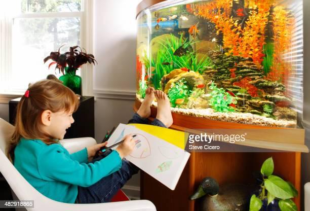 Child drawing fish from aquarium