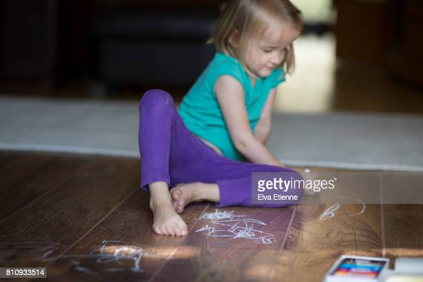 Child drawing on a wooden floor with wax crayons