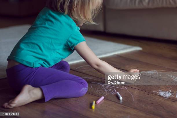 Child drawing on wooden floor with crayons