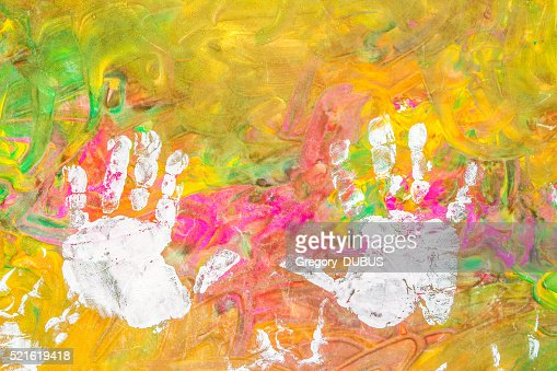 Child drawing painting with his white hands on colorful background