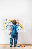 child draws colored paint spots on paper