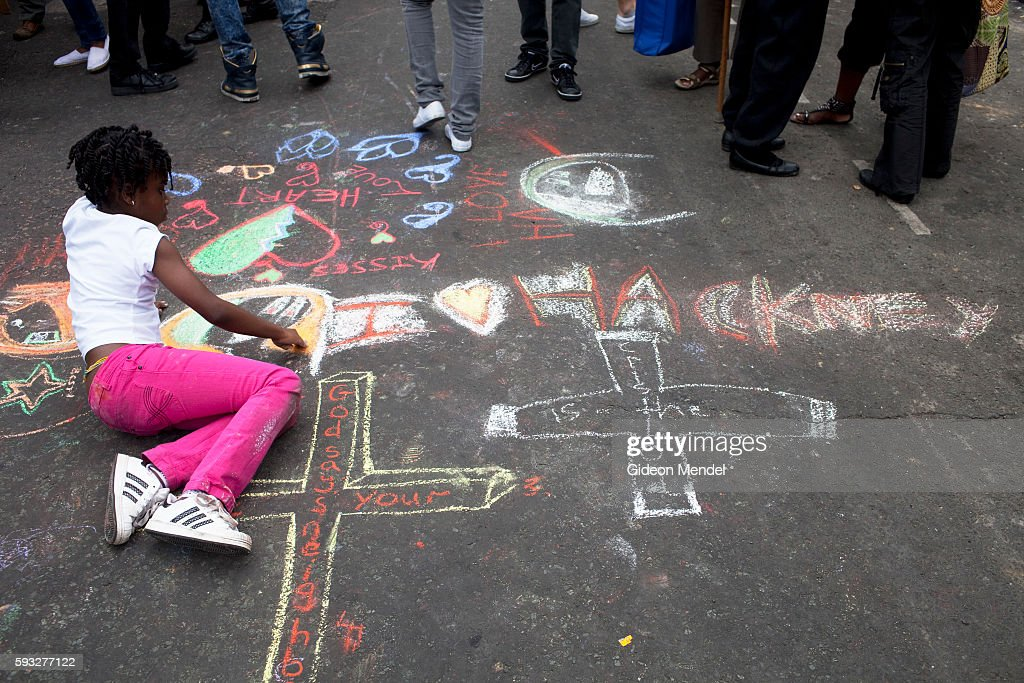 A child draws positive messages on a street which a week earlier had seen violent clashes between local youth and police This scene was at a...