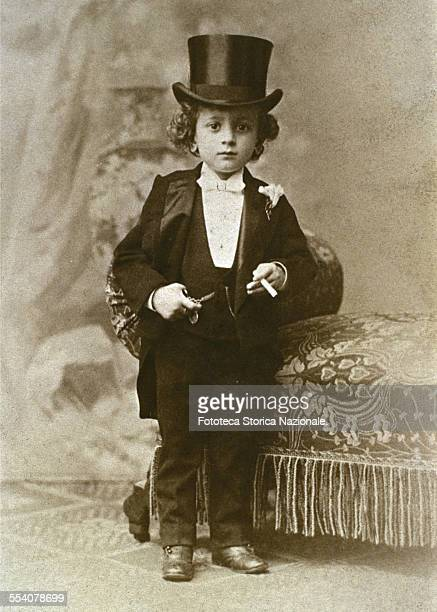 Child dressed as a bon viveur with a top hat white shirt waistcoat and a bow tie In his left hand he holds a cigarette and keeps the right hand in a...