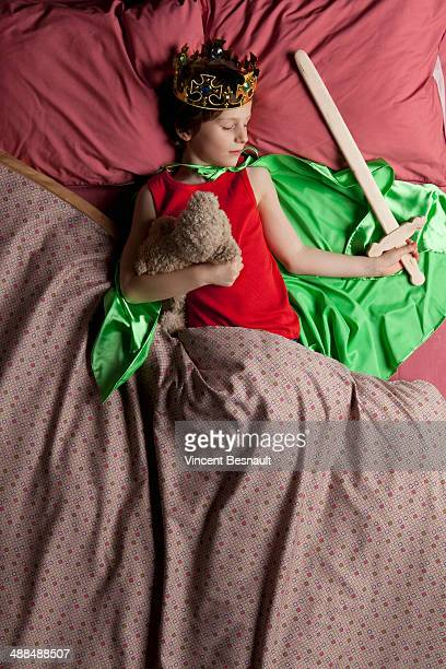 Child dressed as a king sleeping in bed