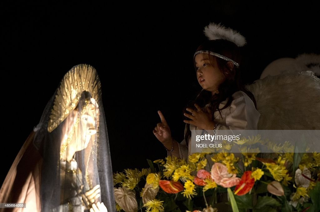 A child dressed as an angel sings beside a veiled statue of Mother Mary during a mass in celebration of Easter Sunday outside St. Domingo Church in Manila on April 20, 2014. Christian believers around the world mark Easter in celebration of the crucifixion and resurrection of Jesus Christ.