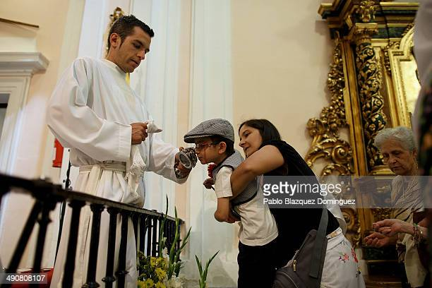 A child dressed as 'Chulapo' kisses a relic of San Isidro during the San Isidro festivities at San Isidro hermitage on May 15 2014 in Madrid Spain...