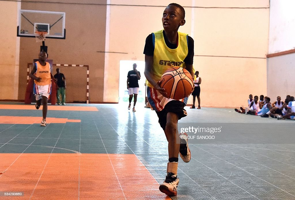 A child dribbles with the ball during a basketball match of the four days of workshop with the American player Tommy Davis organised by the US embassy at the Felix Houphouet-Boigny University in Abidjan on May 25, 2016. / AFP / ISSOUF