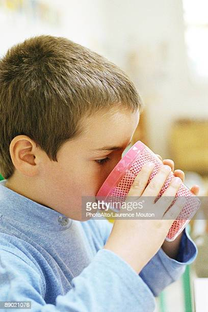 Child drinking from plastic cup, side view