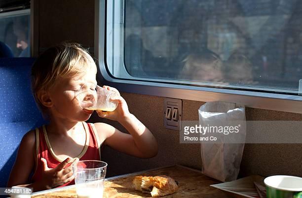 child drinking orange juice in the train
