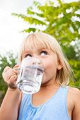 Little girl drinking water looking side in a summer garden