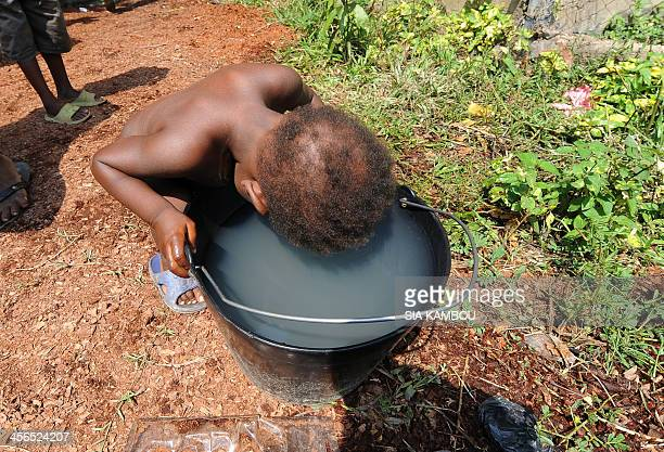A child drinks from a bucket in the catholic youth centre Don Bosco in Bangui on December 14 where thousands of internally displaced people including...