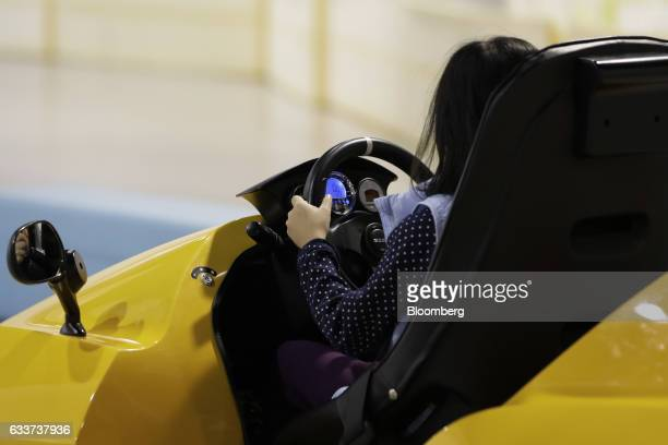 A child drives a Modi Corp Pius micro electric vehicle during a driving experience course inside the Ride Studio at the Toyota Motor Corp Mega Web...