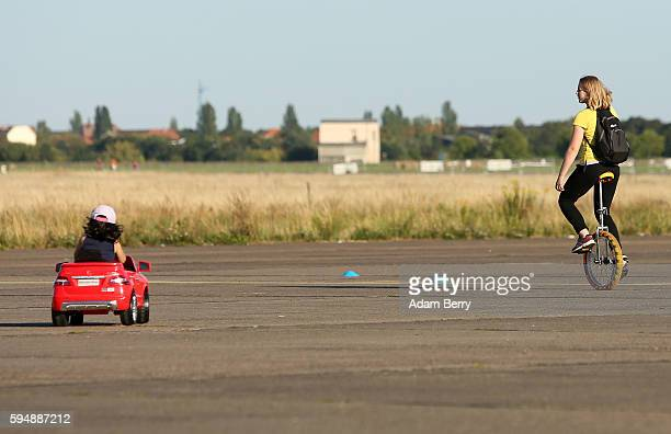 A child drives a toy car as a woman rides a unicycle at the former Tempelhof airport on August 24 2016 in Berlin Germany In a sudden change of...