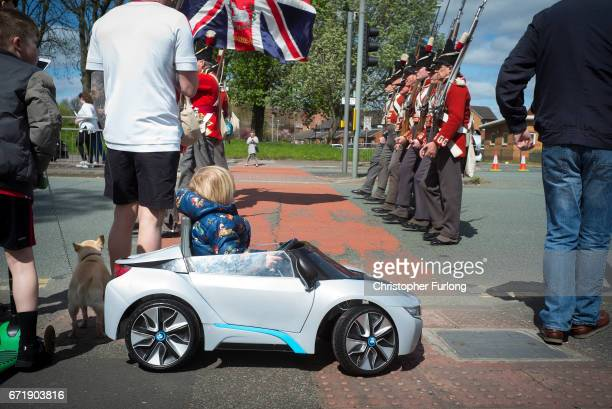 A child drives a toy car as men dressed as soldiers march while families and local residents watch the Manchester St George's Day parade through the...