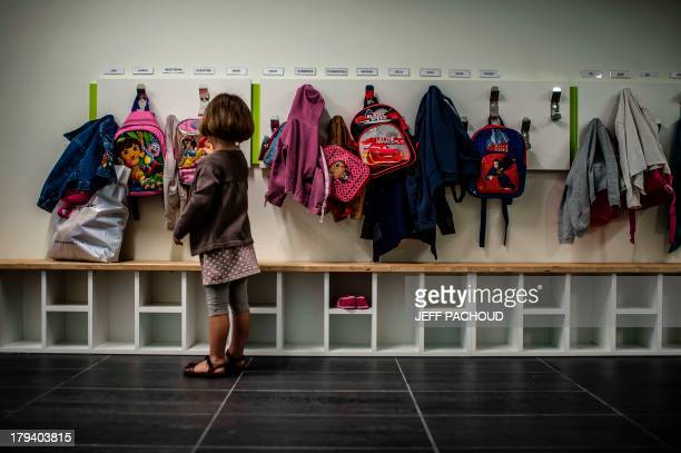 A child drops off her bag as she goes to class on the first day of school following the summer holidays on September 3 2013 in Lyon PACHOUD