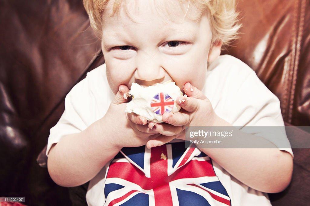 Child eating a Union Jack cupcake : Stock Photo