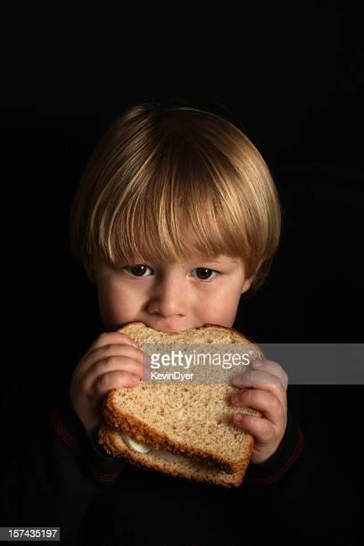 Kind isst ein Ei-Sandwich (isoliert auf schwarz