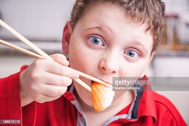 Child eating salmon sushi with chopsticks