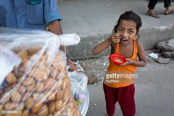 A child eating street food in Dhaka Bangladesh on October 15 2016 Most of time food are being prepared with unhygienic handling And those food are...