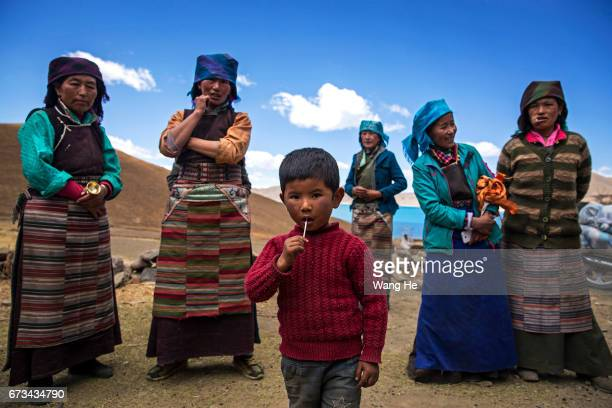 A child eats a lollipop as Tibetan women stand in a village near the Yamdrok Lake on April 26 2017 in Dongla County in the Lhokha Prefecture of Tibet...